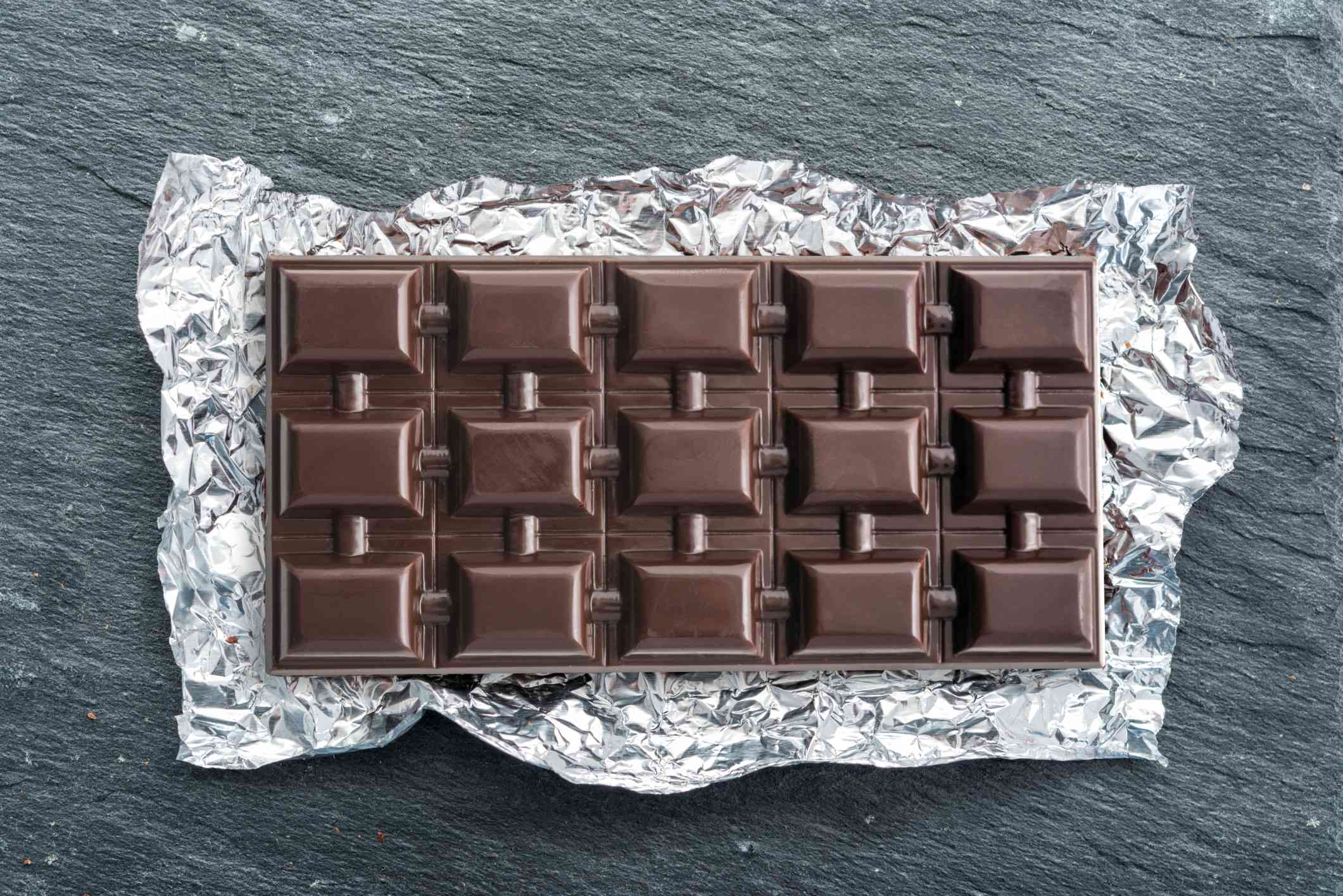 Bar of chocolate in the wrapper on a stone counter