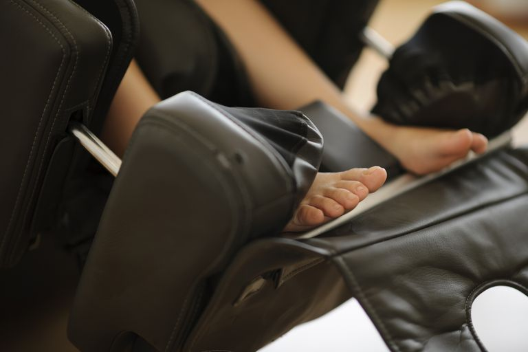 Woman legs in massage chair