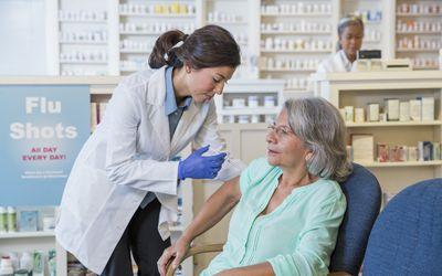Pharmacist giving customer flu shot