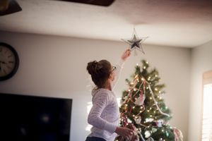 girl putting a star on a Christmas tree