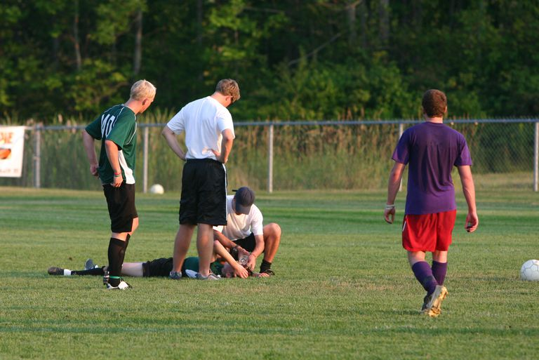 Injured player being helped by an athletic trainer