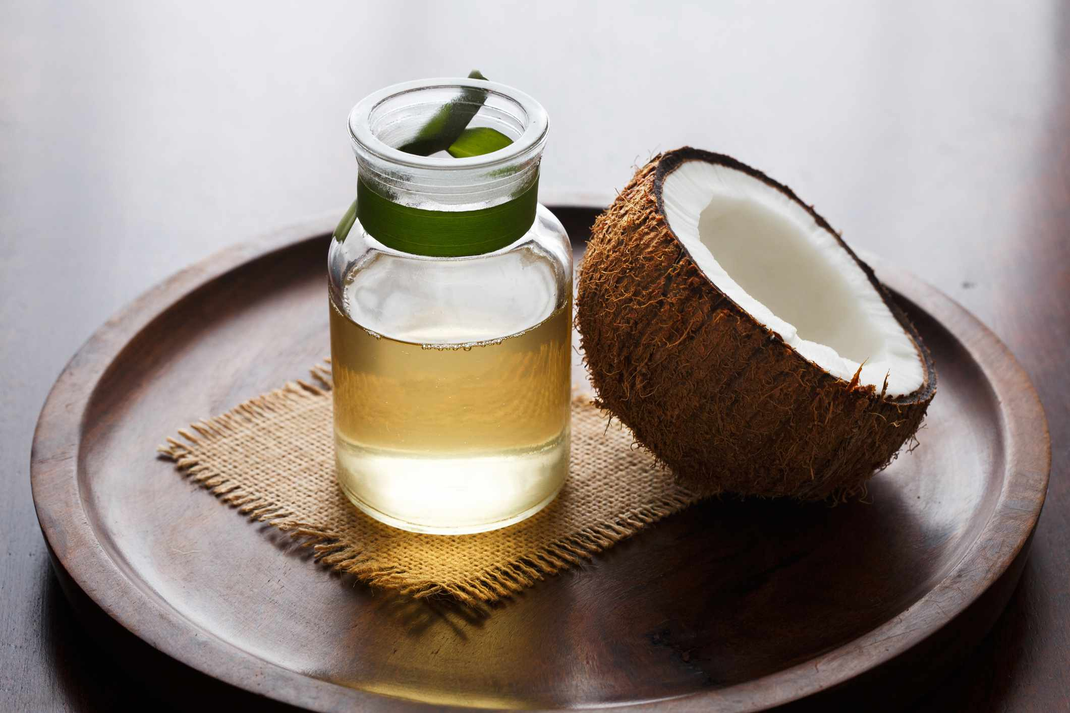 Coconut oil and a coconut half sitting on a tray