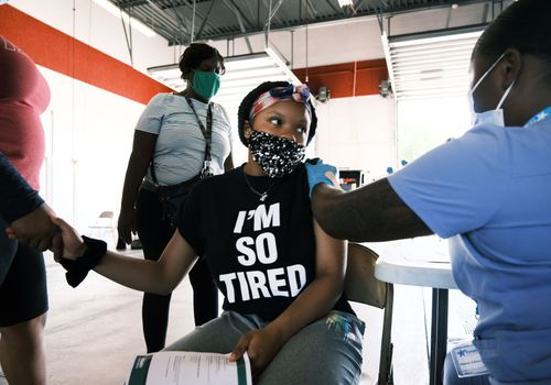 """A woman with a t-shirt that says """"I'm so tired"""" while getting vaccinated"""