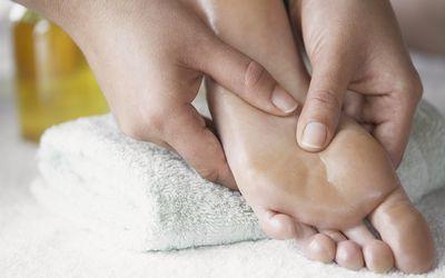 Woman rubbing something into bottom of the feet