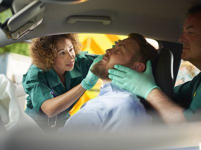 Paramedics treating a car accident patient