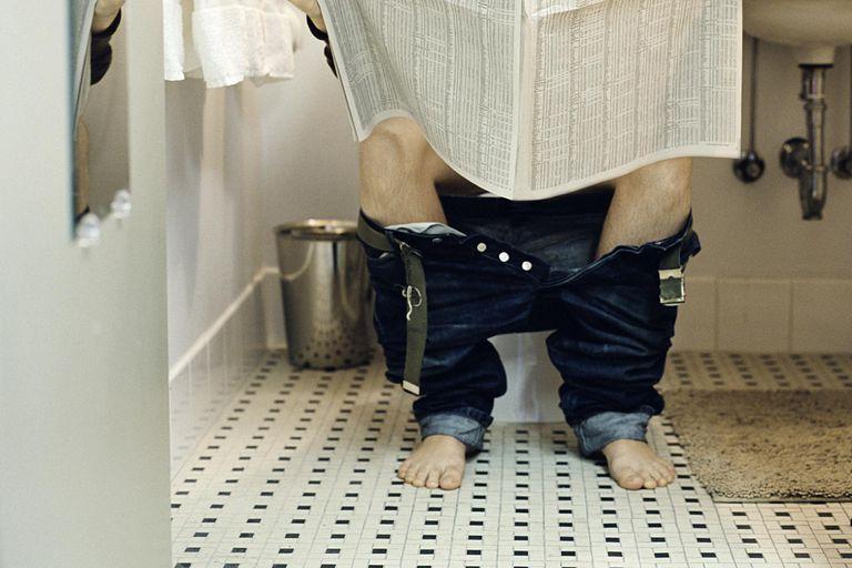 Man Reading on Toilet