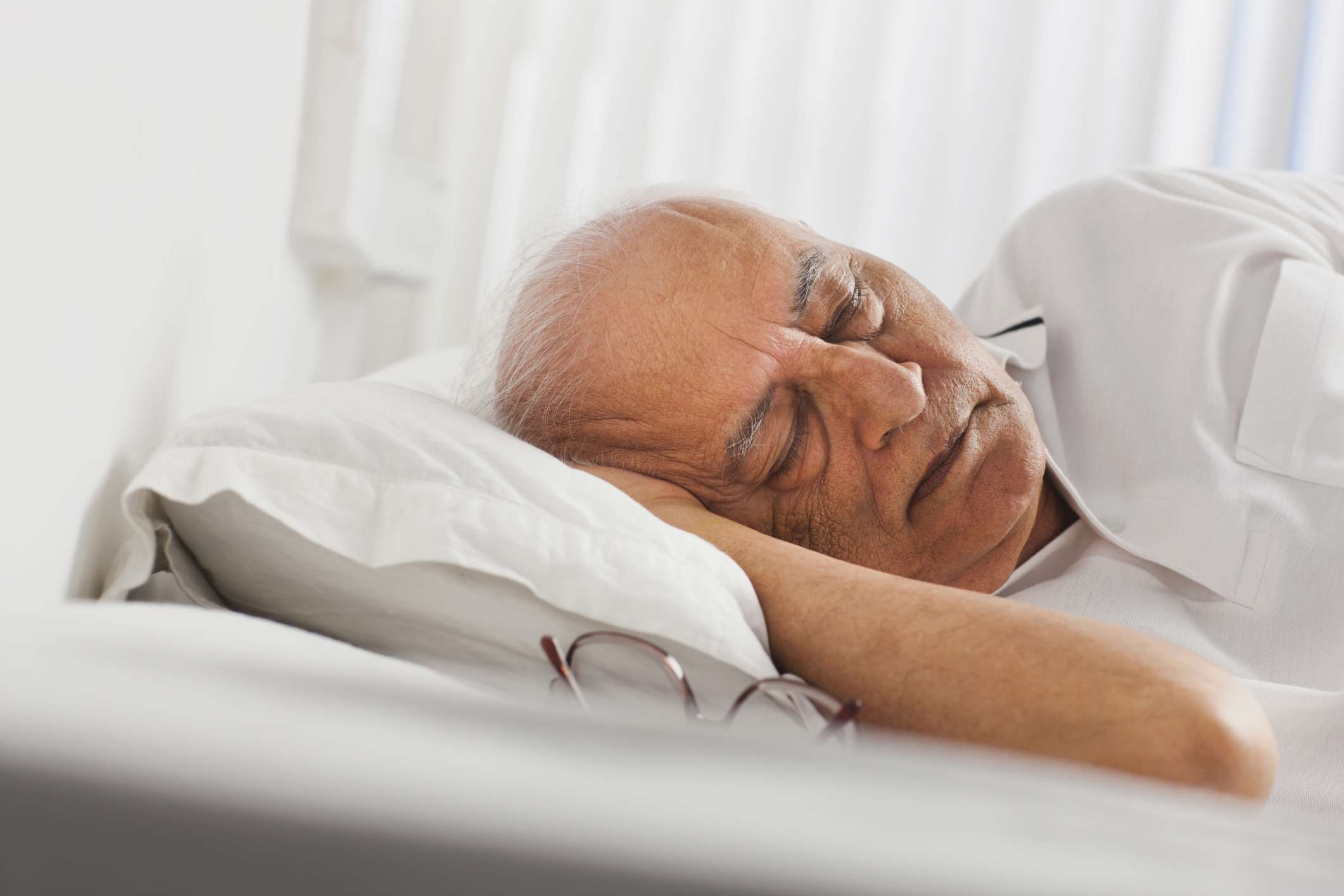 Mature man sleeping in bed next to a pair of glasses