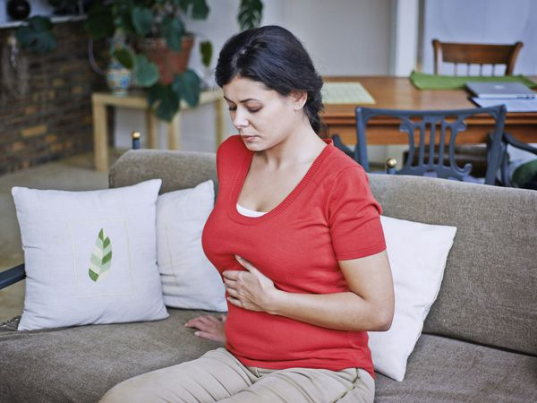 Woman holding her stomach while sitting on a couch