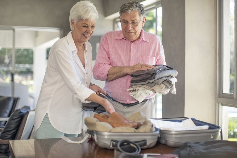 Senior couple packing for a trip together - stock photo