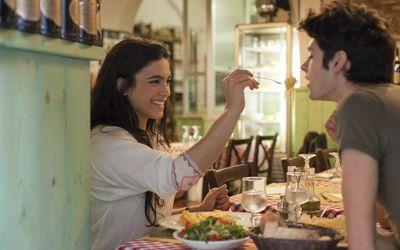 Woman feeding boyfriend in restaurant
