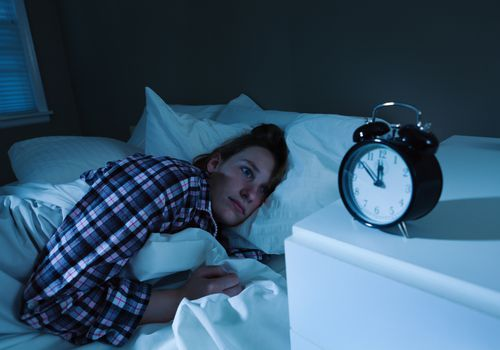 Sleepless Young Woman with Insomnia in Bed, Watching Alarm Clock