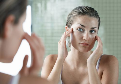 Woman examining face in mirror