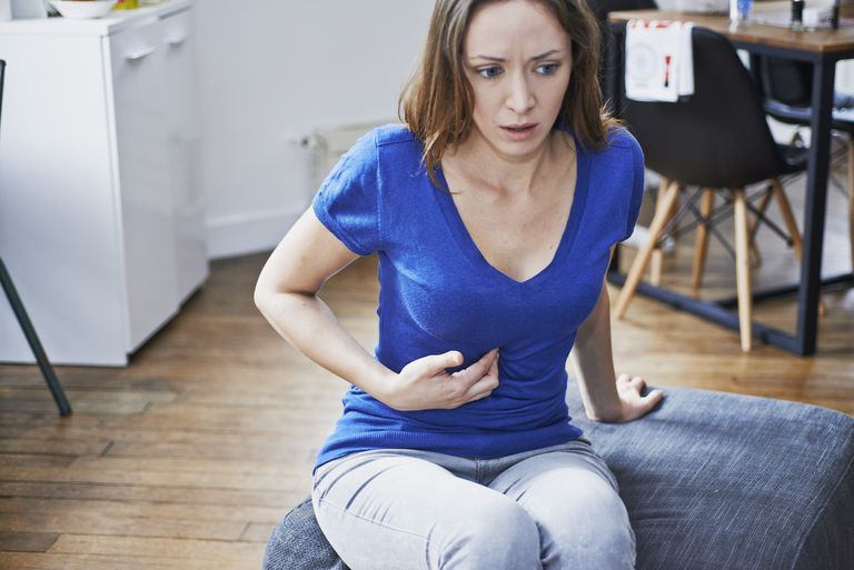 Woman siting on the couch with stomach pains