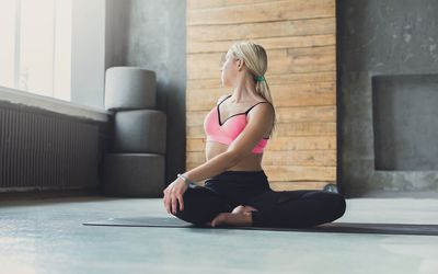Woman in athletic clothing rotating doing spinal rotation in gym