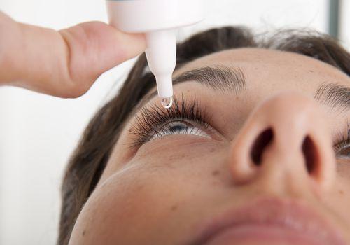 Person applying eye drops.