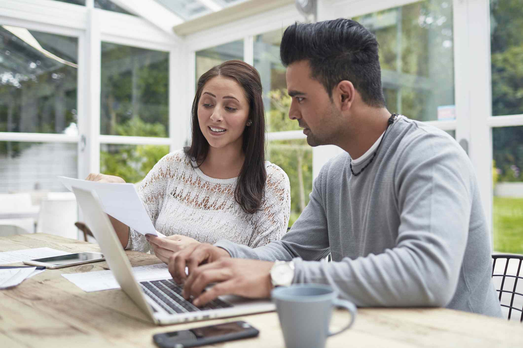 Woman showing document to man using laptop