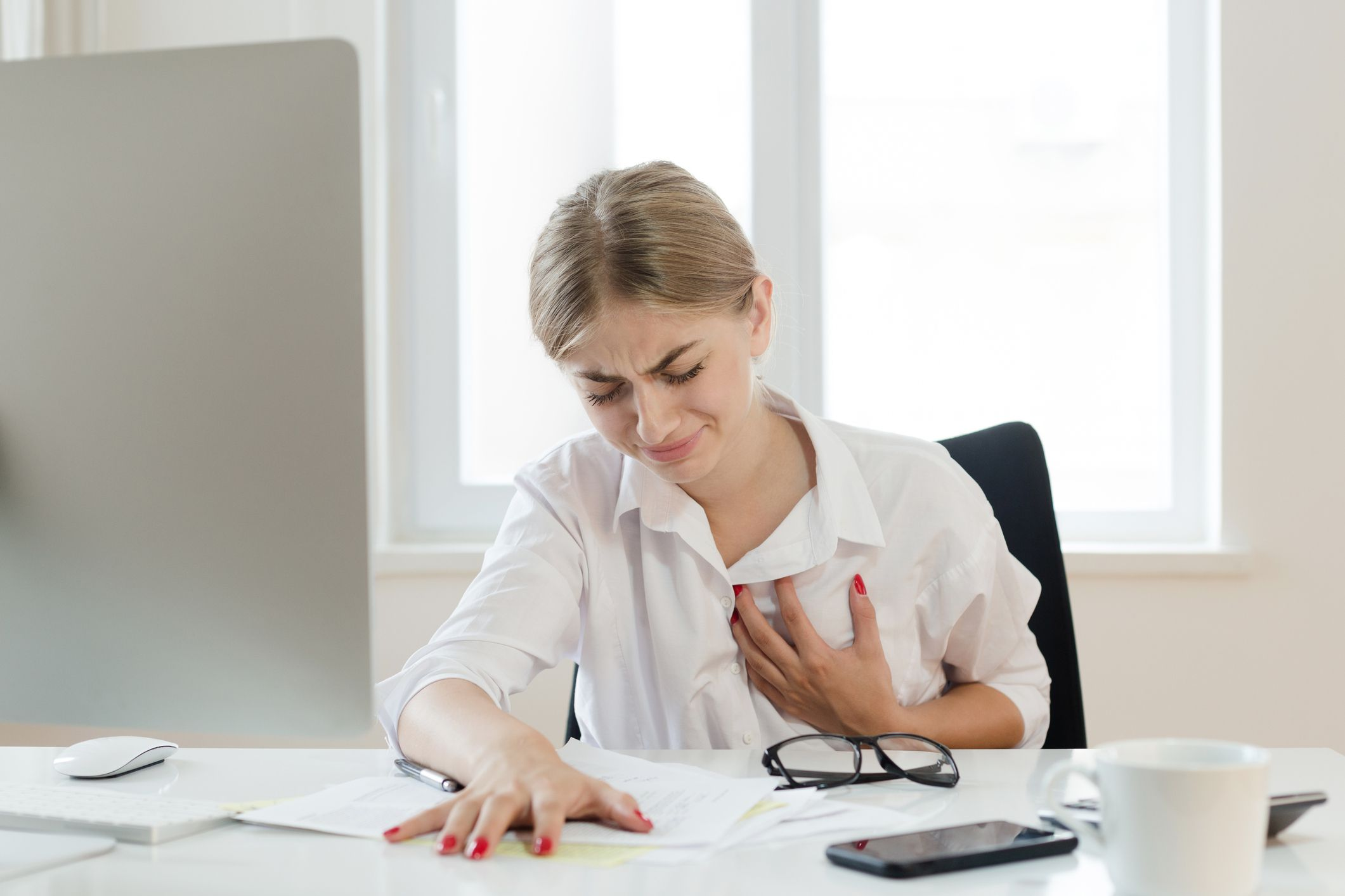 A woman touching her chest in pain