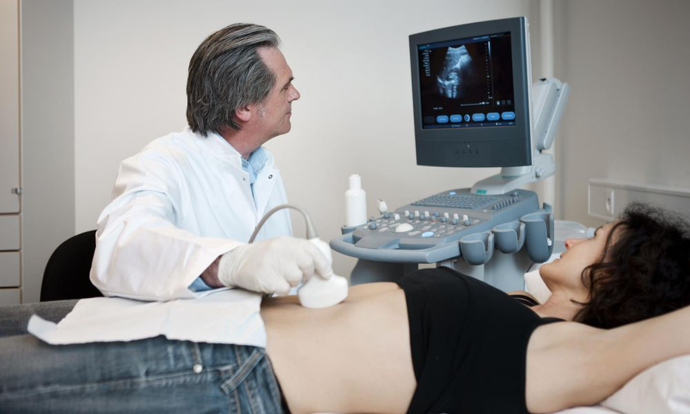 Doctor examining woman with abdominal ultrasound