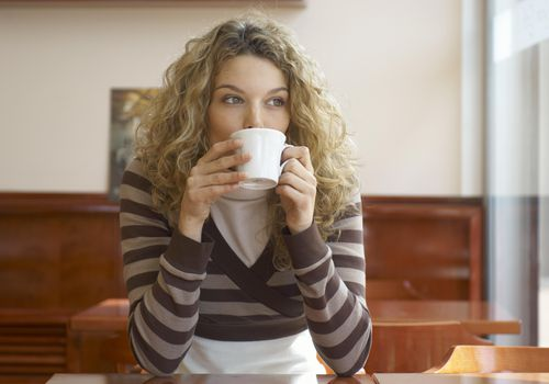 Young woman drinking from coffee cup in cafe