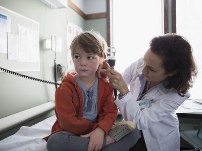 Pediatrician checking ear of boy in examination room