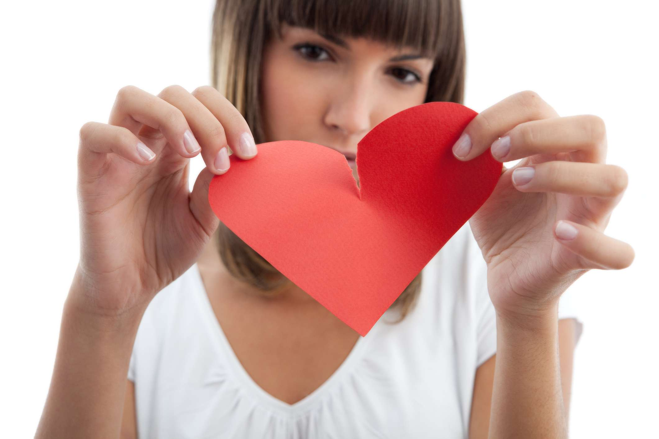 Woman tearing a paper heart in two