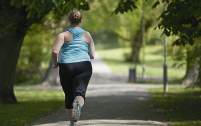 Young woman running on path, rear view