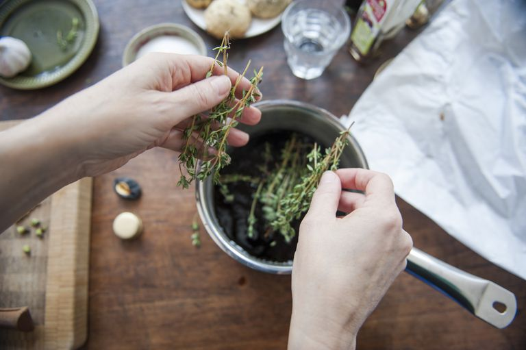 Adding thyme to a cooking pot