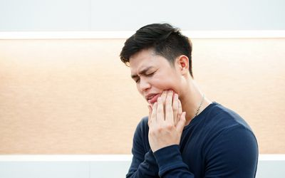 close up adult asian man using hand massage cheek cause from toothache (wisdom tooth) at house , dental health care concept