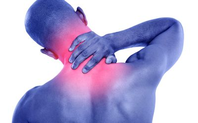 A man stretches his neck to the side while clutching the sore muscles, which are highlighted in red.
