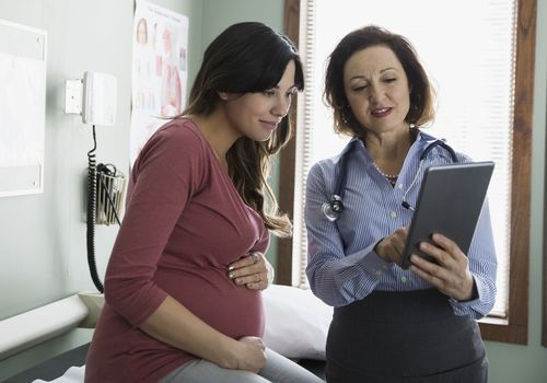 A doctor and a pregnant patient talking and looking at a digital tablet