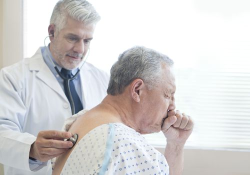Male doctor examining male patient who's coughing