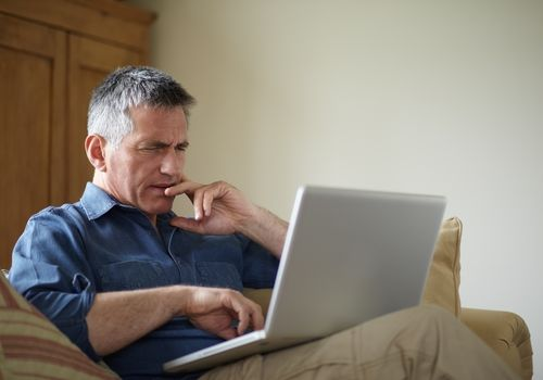Worried man looking at his laptop computer