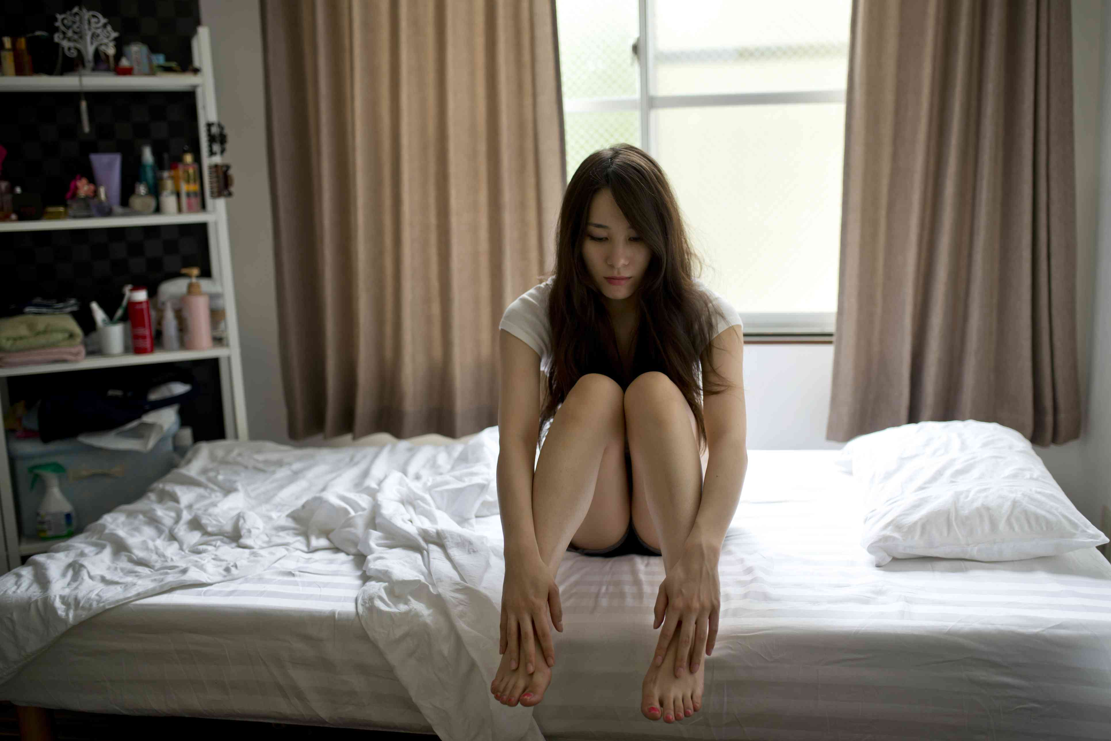 Woman sits on her bed looking at the floor