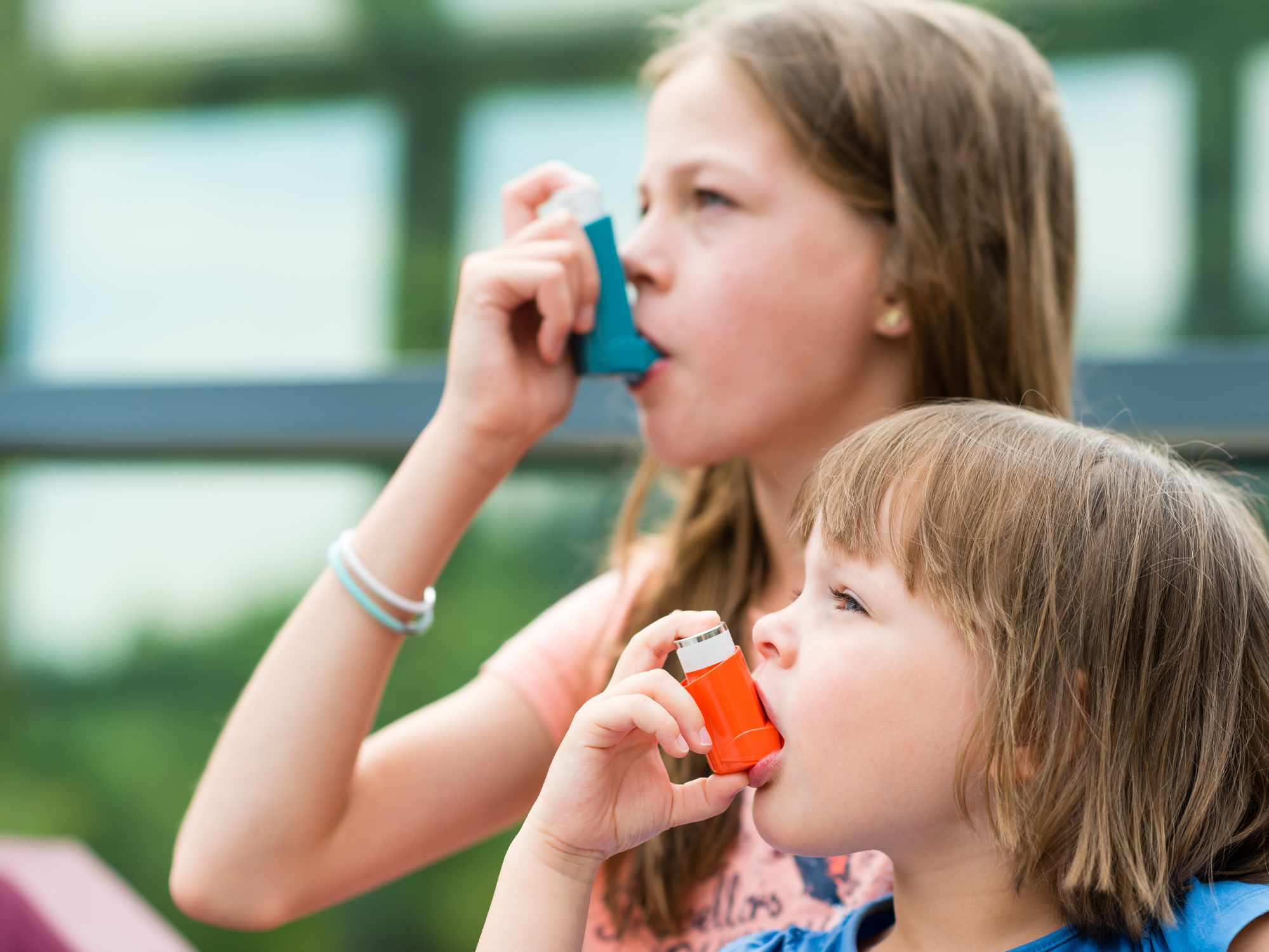 Two girls using their asthma inhalers