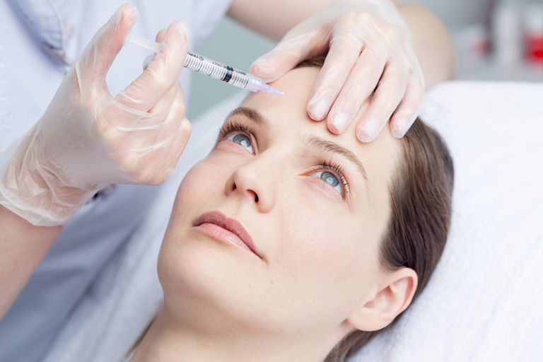 Woman getting Botox injection in forehead