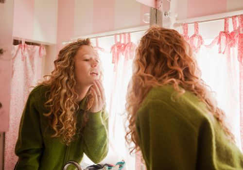 Young woman looking at her skin in the mirror.