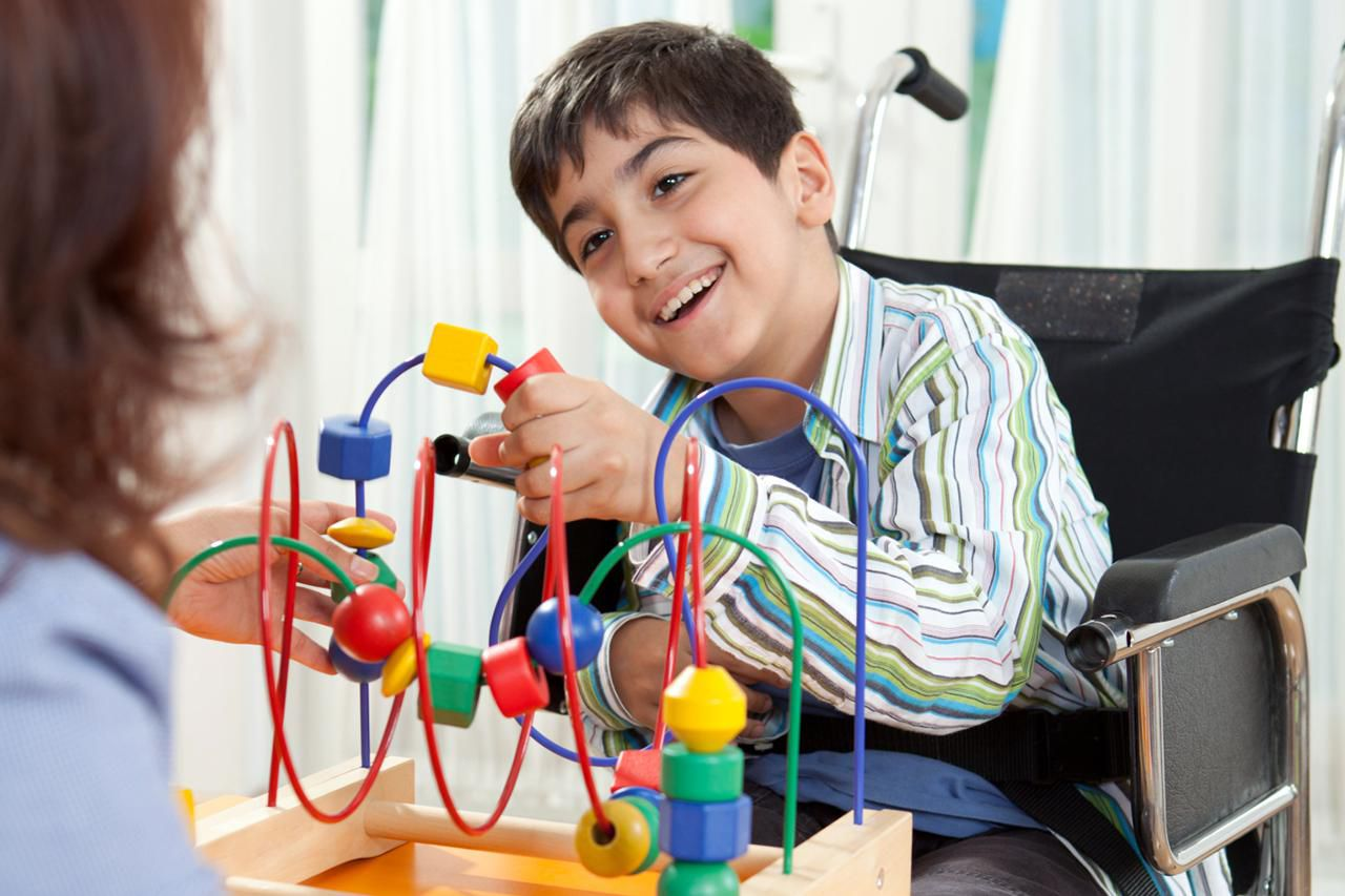 Boy in a wheelchair learning in physical therapy