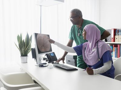 Two physicians discuss an endoscopy photo on a computer screen.