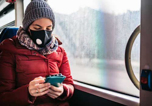 Woman in the winter wearing a face mask.