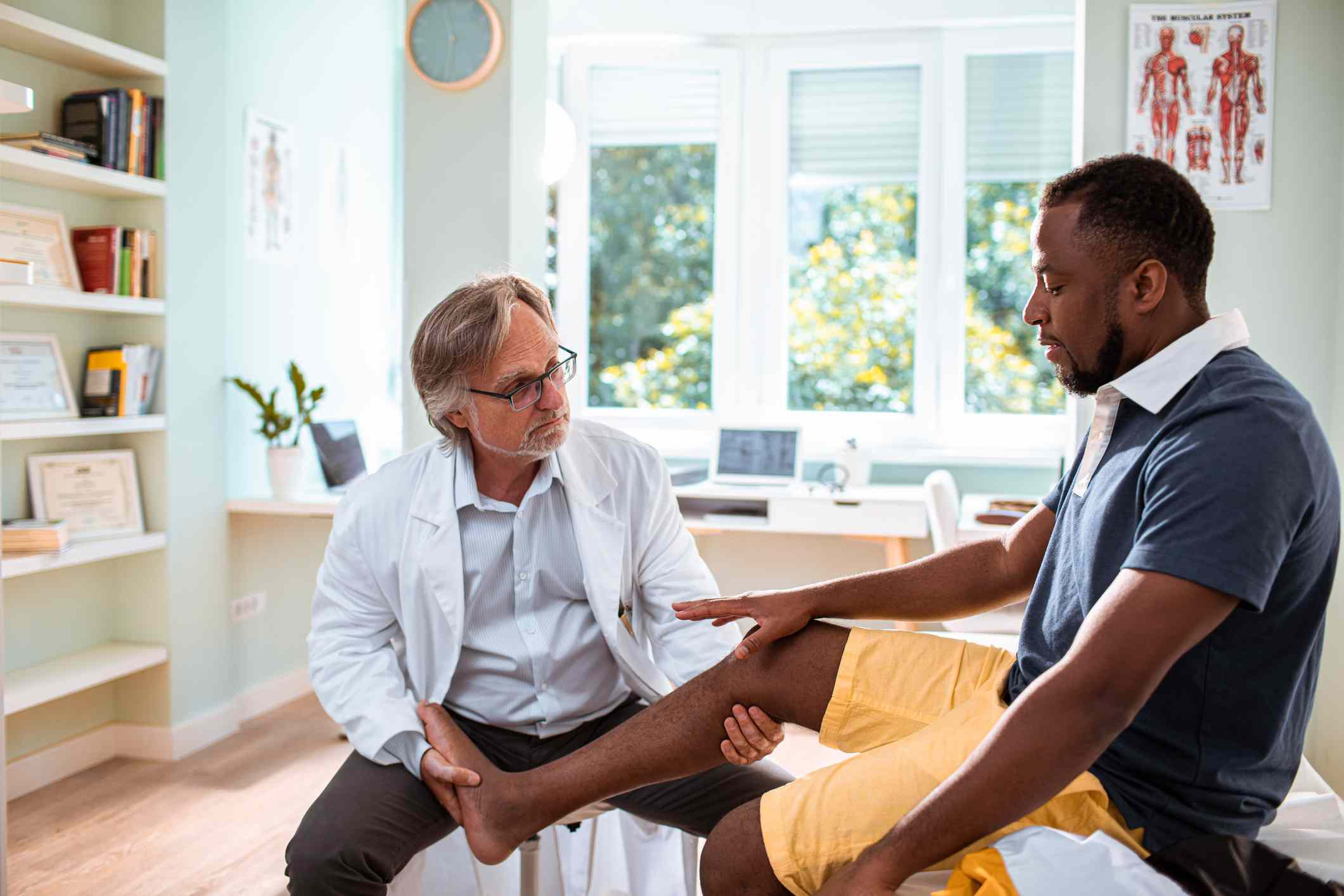 Black patient discusses joint pain with doctor