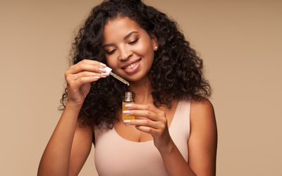 Women holding tube of essential oil