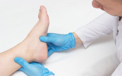 Doctor examines the patient's leg with heel spurs, pain in the foot, white background, close-up, plantar fasciitis