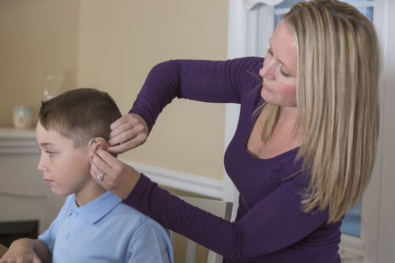 Caucasian mother fitting deaf son with hearing aid