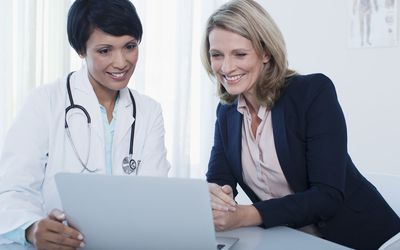 Doctor and patient using laptop in hospital office