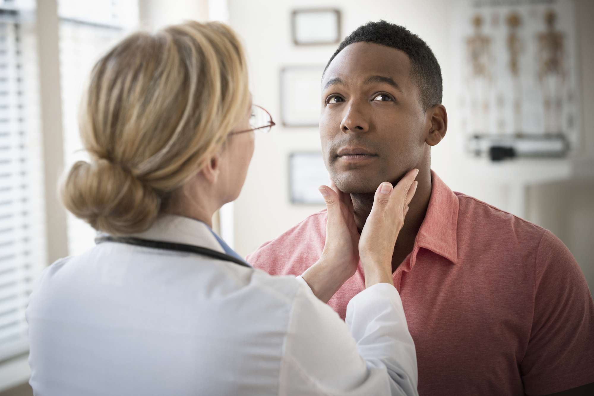Doctor examining throat of patient in clinic