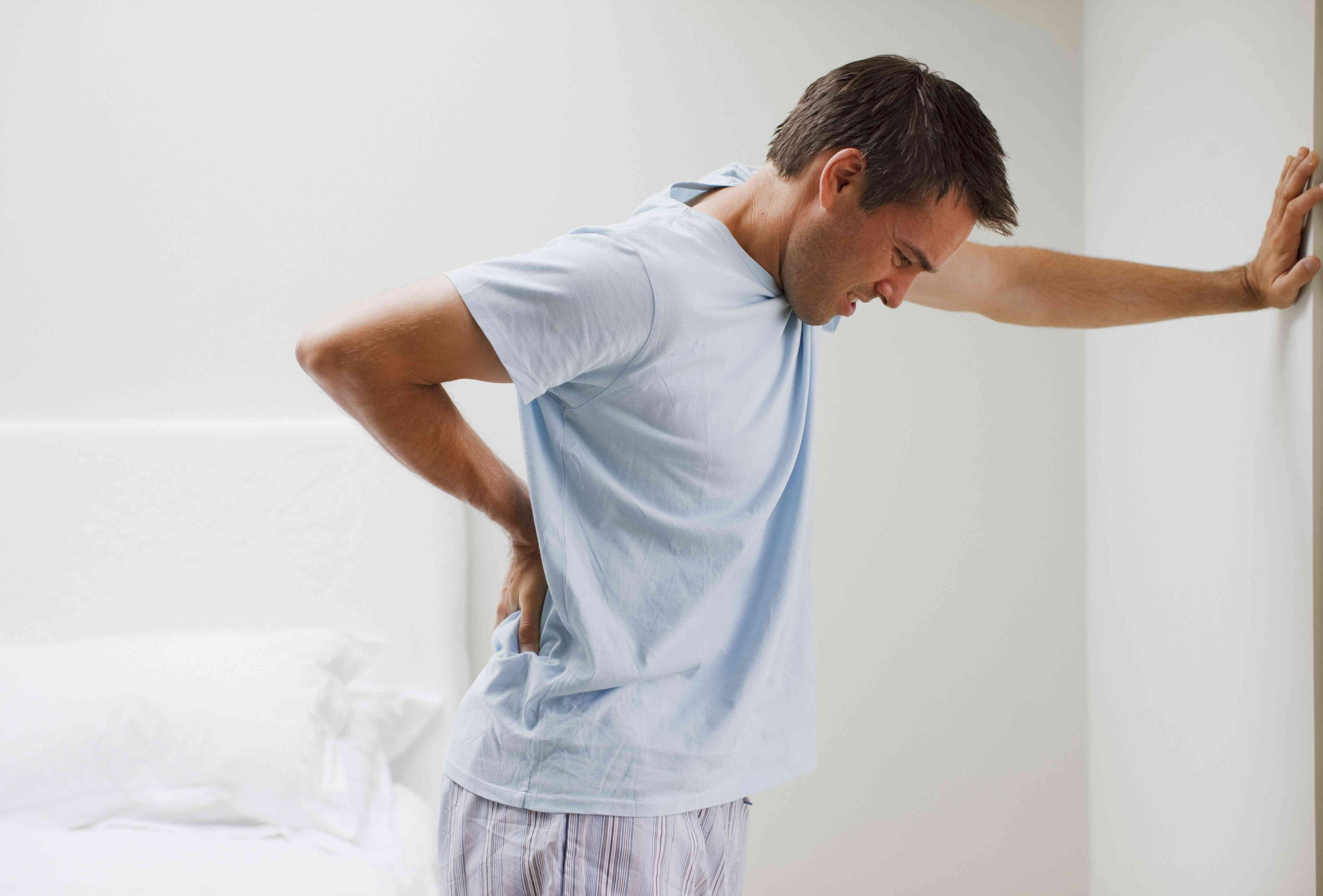 Man with back pain leaning against a wall