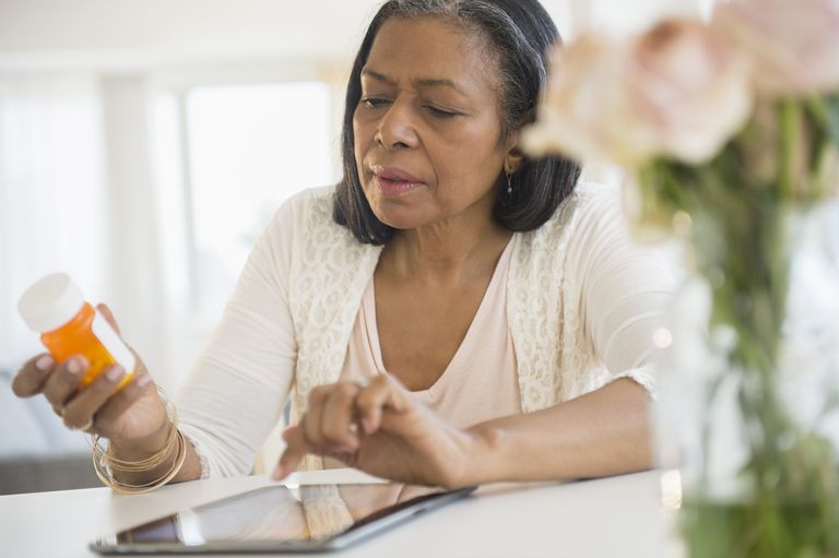 Mixed race woman researching medication on tablet computer