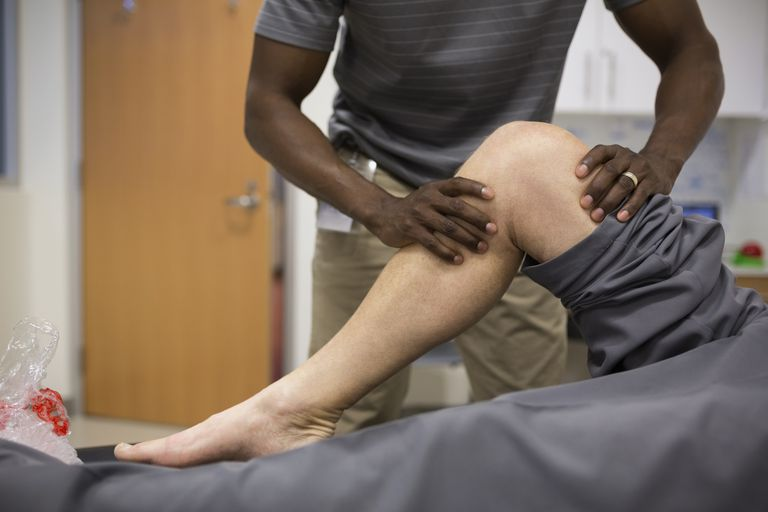 A physical therapist works on a patient's leg.