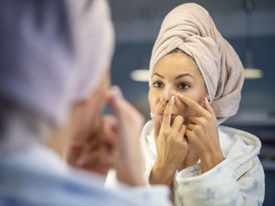 Young woman and her morning beauty routine. She is squeezing her pimple.