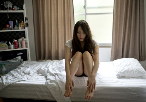 A woman sitting pensively on a bed